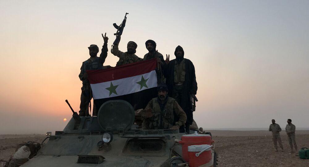 Forças sírias gesticulam enquanto carregam a bandeira nacional na vila de Suwayyah, perto da cidade fronteiriça com síria de Albu Kamal, em 9 de novembro de 2017