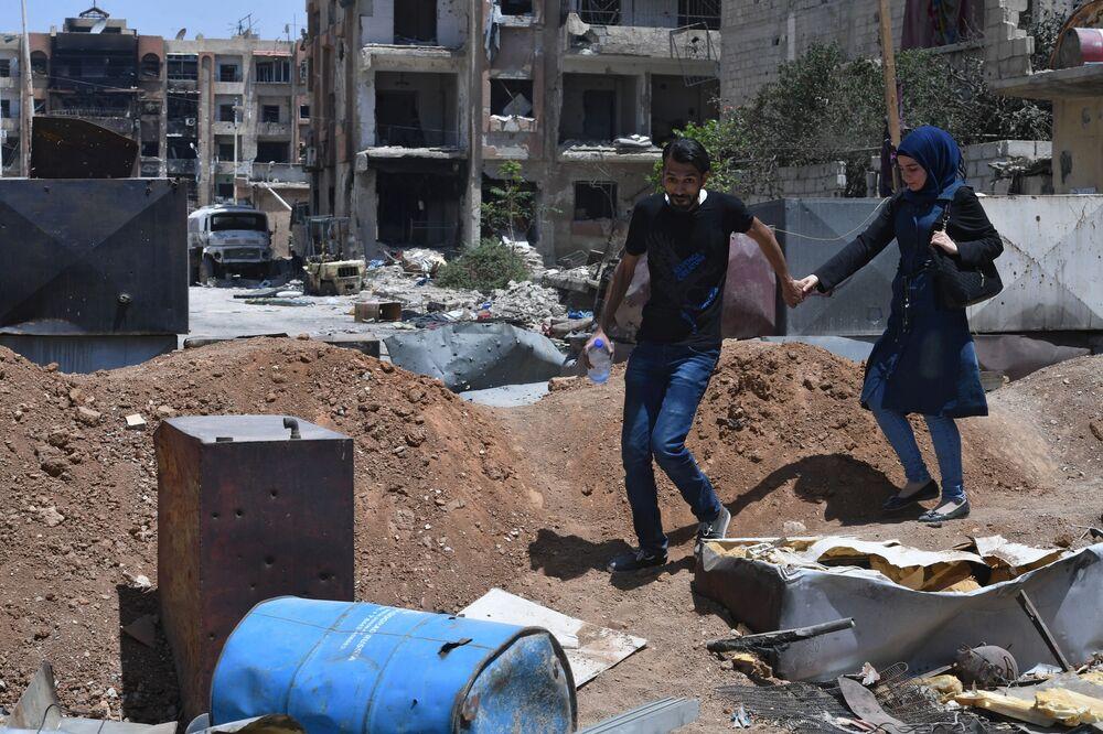 Pessoas andando pelo território do antigo campo de refugiados Yarmuk, na Síria