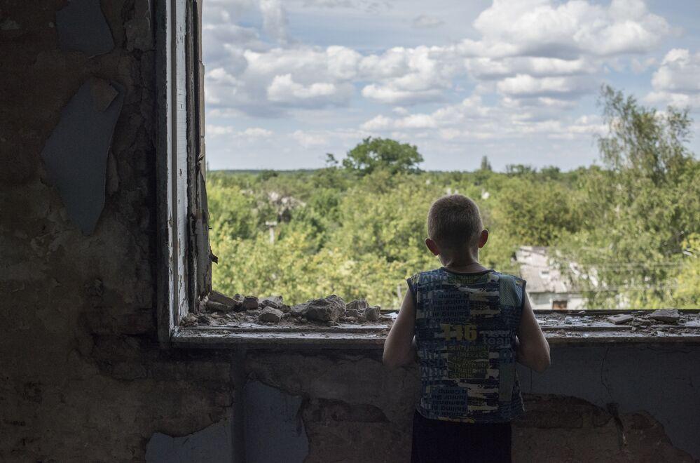 Menino dentro de um ginásio escolar devastado, que se tornou abrigo para refugiados, na cidade de Gorlovka, autoproclamada República Popular de Donetsk
