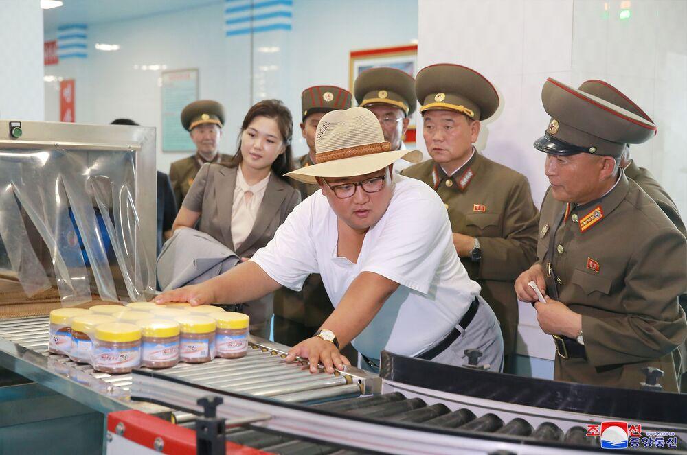 O líder norte-coreano, Kim Jong-un, inpeciona produtos na esteira de uma fábrica de peixes em conserva na Coreia do Norte.