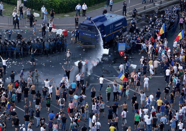 Polícia usa um canhão de água contra milhares de romenos em um protesto contra o governo na capital Bucareste, 10 de agosto de 2018.