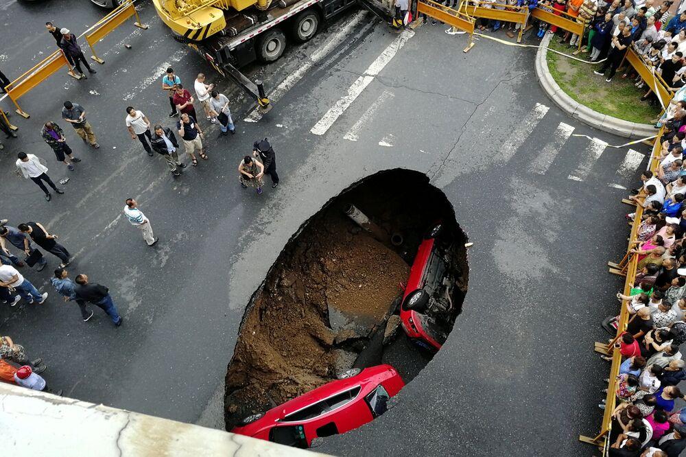 Automóveis caídos em um buraco na estrada, na cidade chinesa de Harbin