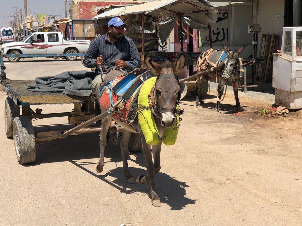 Homem dirigindo carroça em um campo de refugiados na Jordânia