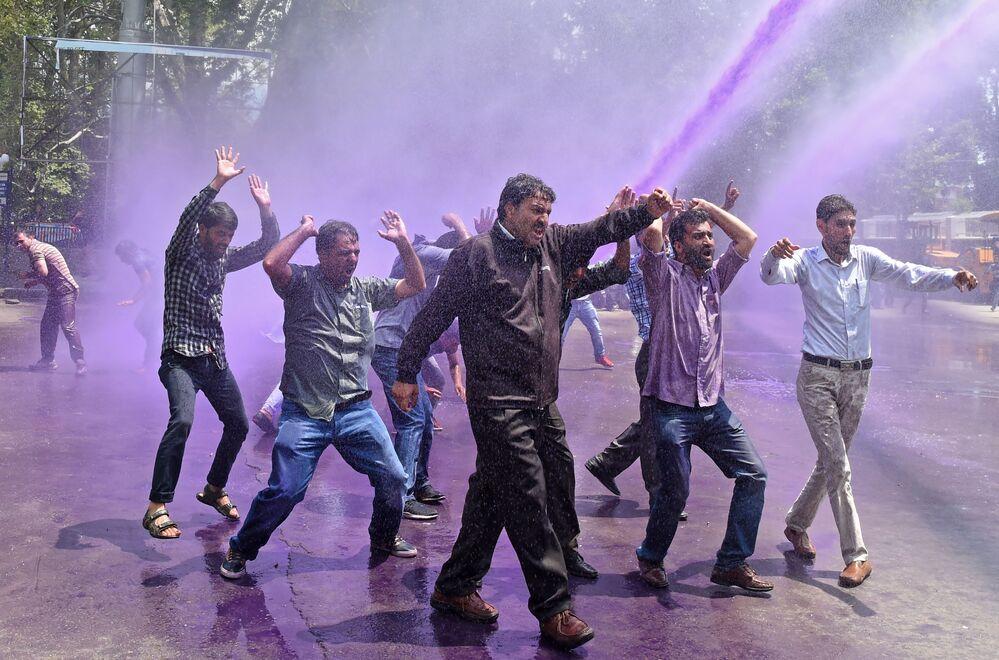 Professores de Caxemira são atingidos por água colorida disparada pela polícia indiana durante um protesto em Srinagar, na Índia
