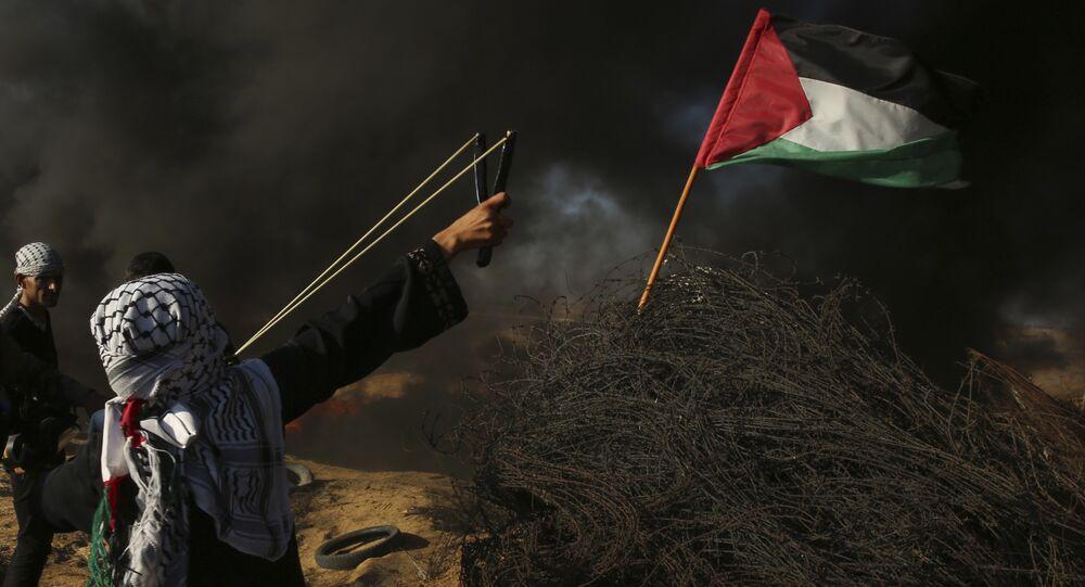 Uma manifestante arremessa uma pedra enquanto outros queimam pneus perto da cerca da fronteira com Israel, durante um protesto a leste de Khan Younis, no sul da Faixa de Gaza, 10 de agosto de 2018.