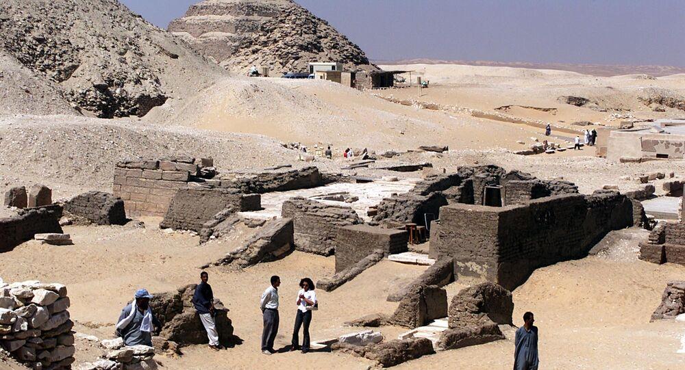 Arqueólogos e trabalhadores são vistos no local dos túmulos de 3.500 anos perto da pirâmide de Saqqara, no Egito, a cerca de 30 km a sul de Cairo, em 6 de junho de 2002 (imagem referencial)