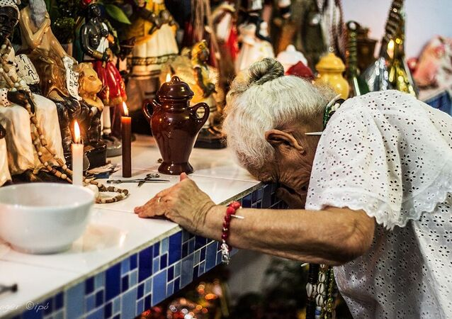 Uma senhora idosa durante ritual religioso de matriz africana.