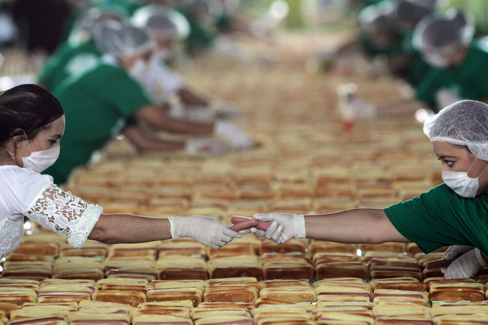 Pessoas preparando centenas de cachorros-quentes em uma tentativa de quebrar o recorde Guinness em Guadalajara, México, em 12 de agosto de 2018