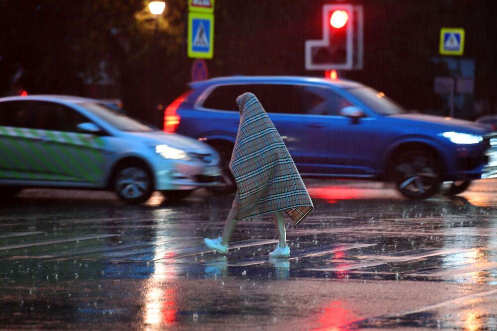Pedestre passa pela rua durante a chuva, protegido com um cobertor, em Moscou