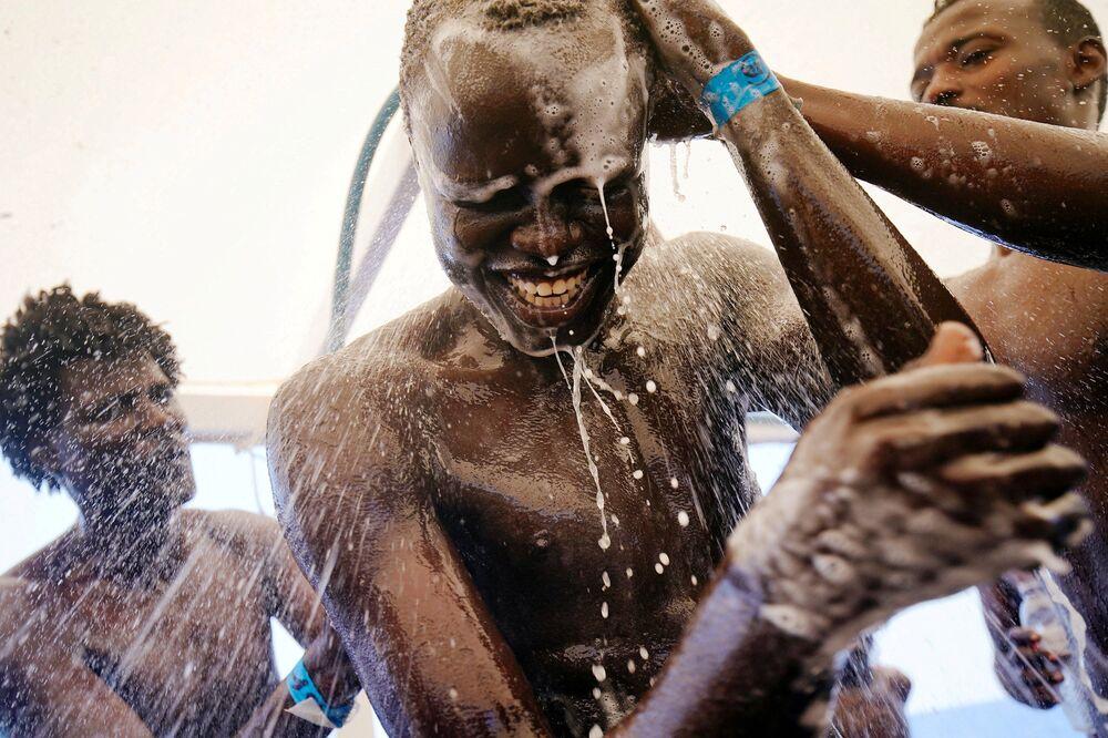 Chuol, de 17 anos, do Sudão toma banho a bordo do barco de resgate espanhol no mar Mediterrâneo, em 3 de agosto de 2018