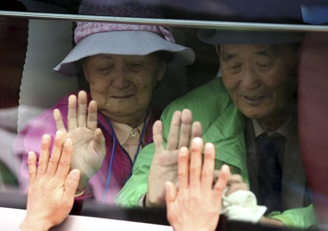 Sul-coreanos em um ônibus tocam a janela na tentativa de sentir as mãos de seus parentes norte-coreanos ao se despedirem após o Encontro da Reunião de Famílias Separadas no resort Diamond Mountain na Coreia do Norte. (Arquivo)