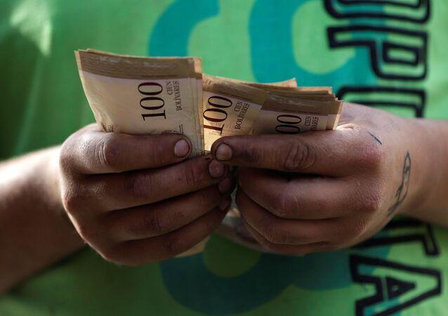 Um caixa conta notas de bolívar venezuelano em um mercado de rua no centro de Caracas, Venezuela (arquivo)