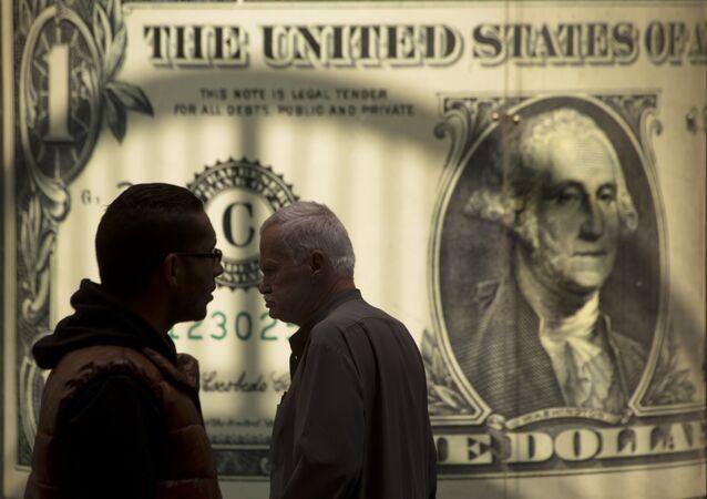 Pessoas passam por um pôster mostrando o dólar americano fora de uma casa de câmbio