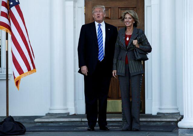 Secretária Betsy DeVos ao lado do presidente estadunidense Donald Trumo