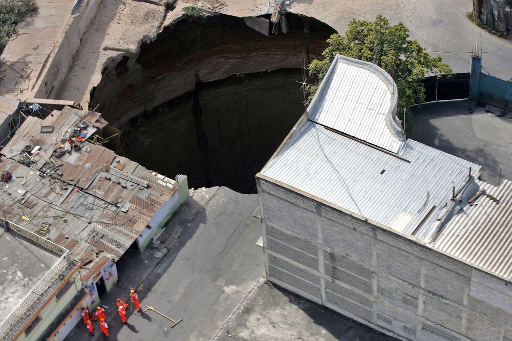Vista aérea de uma enorme cratera de 60 metros de profundidade que surgiu no centro da Cidade de Guatemala, engolindo um prédio