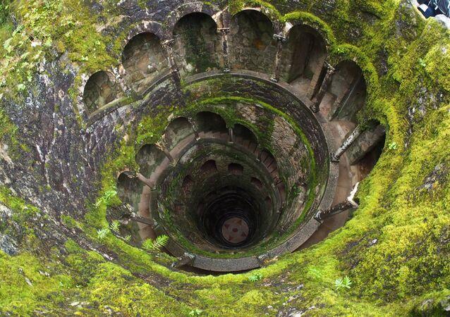 Olhando para dentro do Poço Iniciático – galeria subterrânea de mais de 26 metros de profundidade com uma escadaria em espiral na vila de Sintra, Portugal