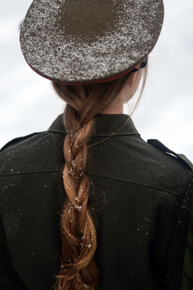 Garota em uniforme militar olhando para um monumento dedicado à milícia popular da Guerra Patriótica de 1812 na cidade de Nizhny Novgorod