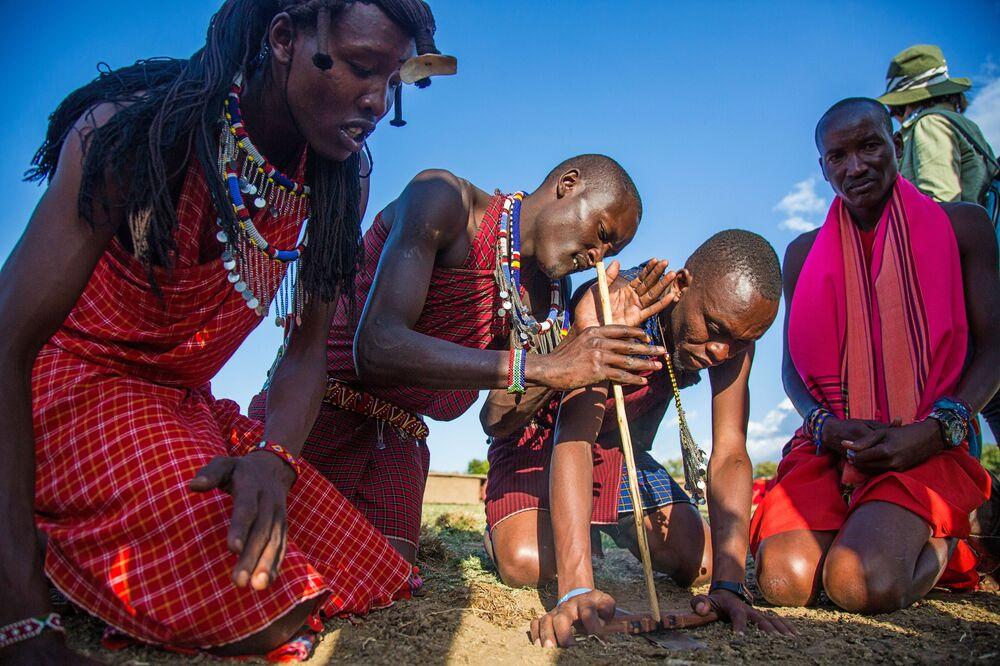 Homens da tribo masai tentam produzir fogo em um povoado de Masai Mara, no Quênia