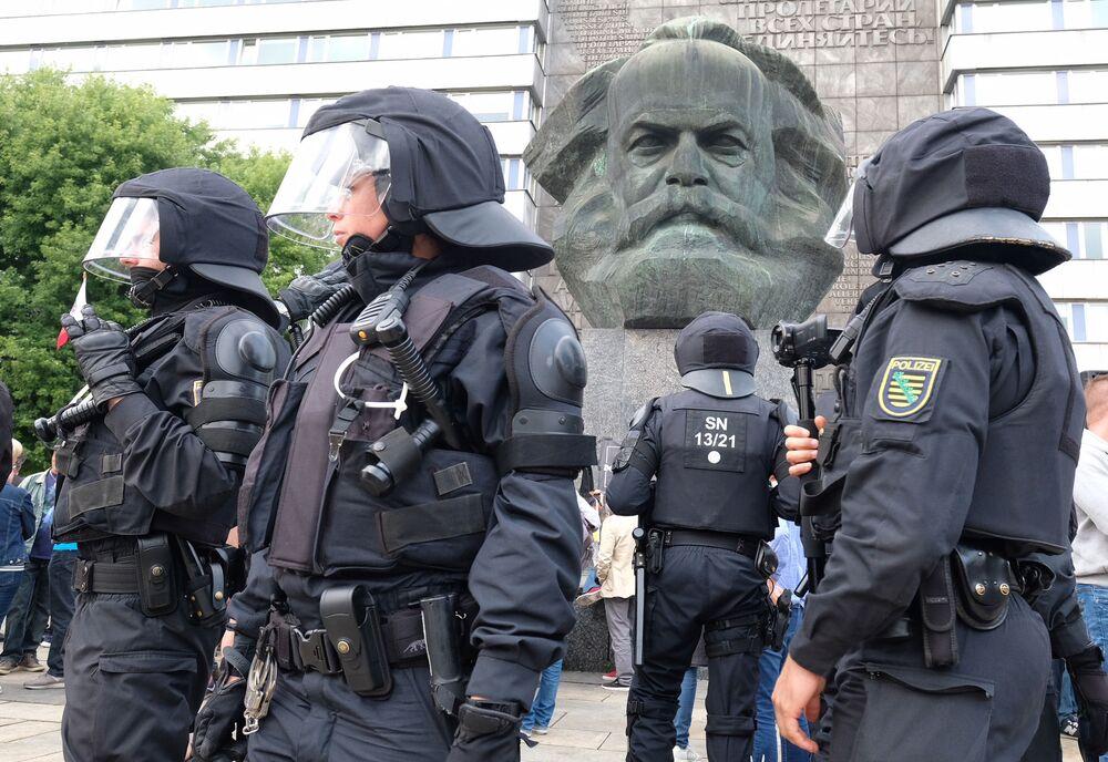 Patrulha policial junto ao monumento de Karl Marx durante os protestos em massa na Saxônia, na Alemanha, após uma disputa entre representantes de várias nacionalidades que provocou a morte de um homem