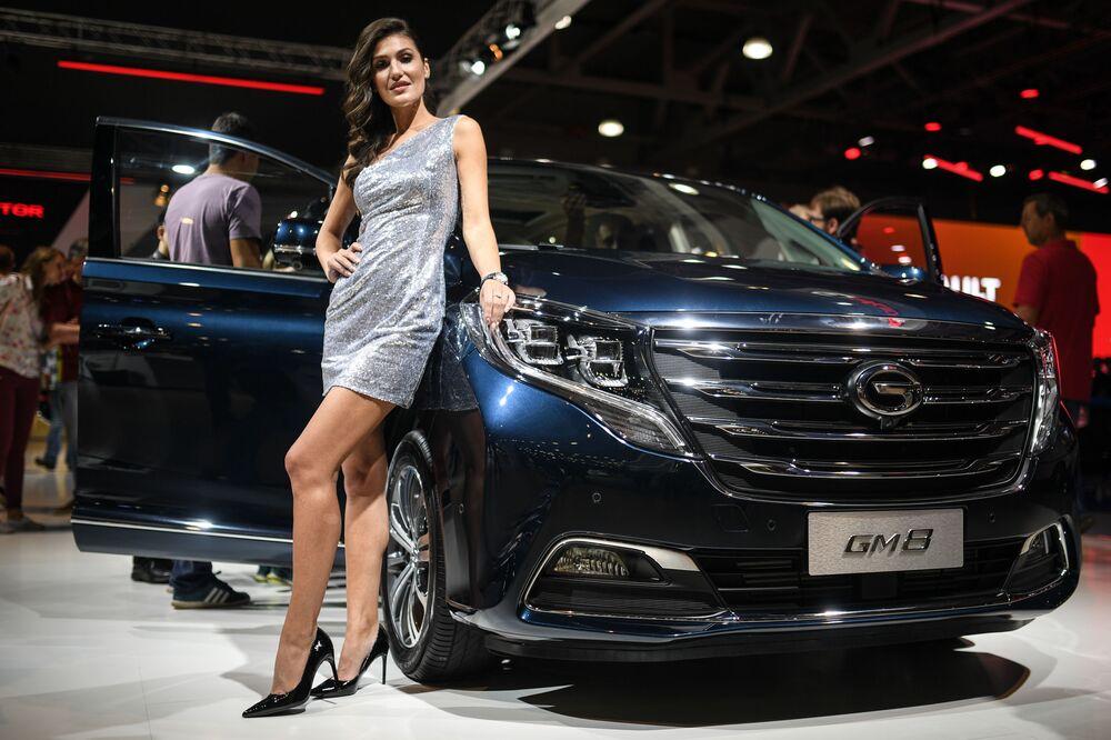 Modelo posa ao lado do GM8, um minivam fabricado pela chinesa GAC