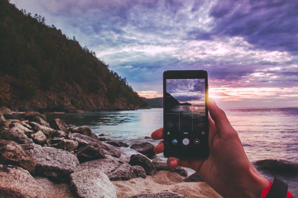 Celular tira foto da magnífica paisagem do lago Baikal (sul da Sibéria), através do qual é possivel ver o pôr do sol e parte da montanha