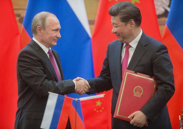O presidente russo, Vladimir Putin (à esquerda) e o presidente da República Popular da China, Xi Jinping (à direita) apertam as mãos durante um cerimônia de assinatura de documentos após conversas bilaterais em Pequim.