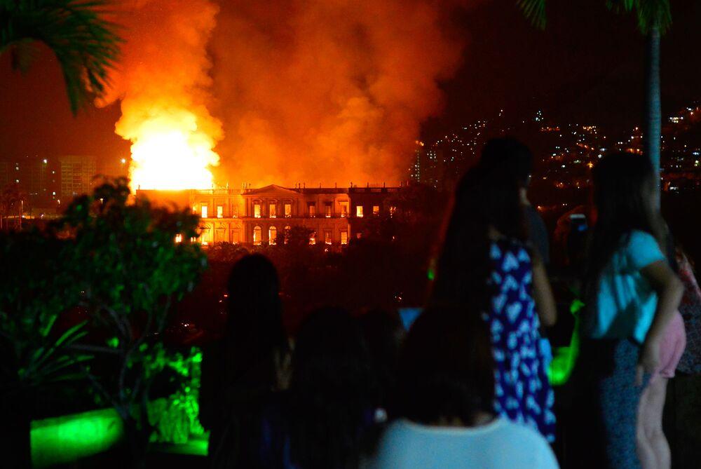 Pessoas observam enorme incêndio no Museu Nacional do Rio de Janeiro, um dos museus mais antigos do Brasil, em 2 de setembro de 2018