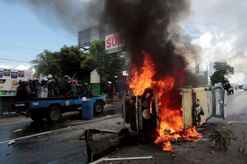 Policiais de choque passam por carro da polícia durante protesto contra o governo do presidente da Nicarágua, Daniel Ortega, na capital Manágua