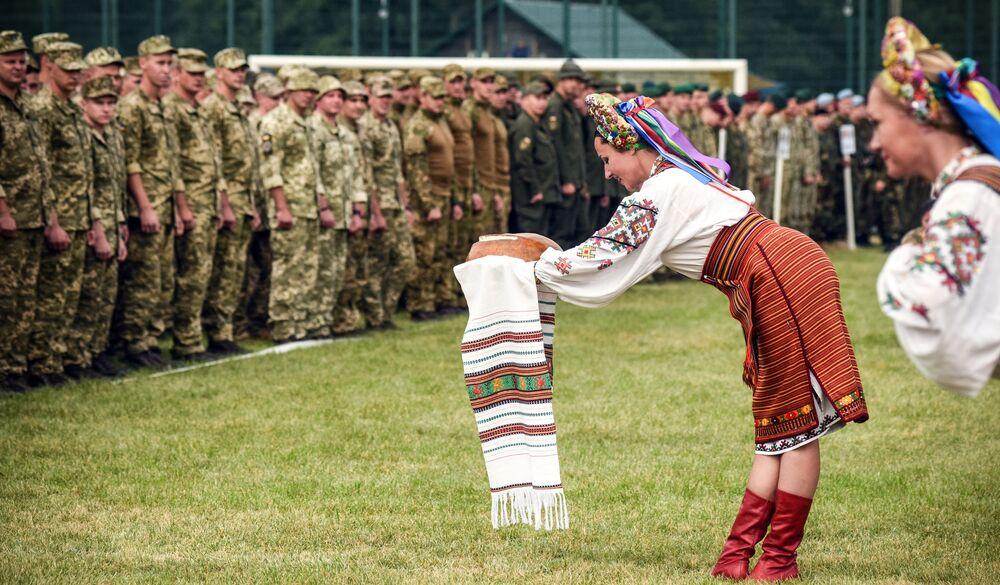 Mulheres ucranianas tradicionalmente vestidas oferecem pão e sal dando boas-vindas a recrutas da OTAN no campo de treino na Ucrânia