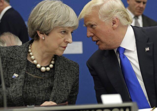 Primeira-ministra do Reino Unido, Theresa May (à esquerda) fala com o presidente dos EUA, Donald Trump (à direita) durante um jantar da OTAN em Bruxelas.