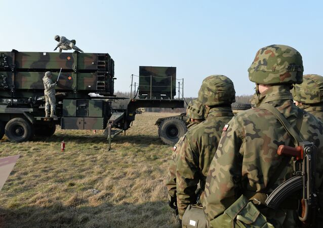 Polish soldiers watch as US troops from the 5th Battalion of the 7th Air Defense Regiment emplace a launching station of the Patriot air and missile defence system at a test range in Sochaczew, Poland, on March 21, 2015.
