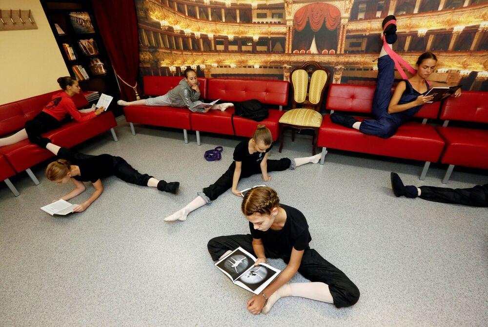 Alunas se exercitam enquanto estudam para teste durante intervalo na faculdade de coreografia Krasnoyarsk, Rússia, em 12 de setembro de 2018