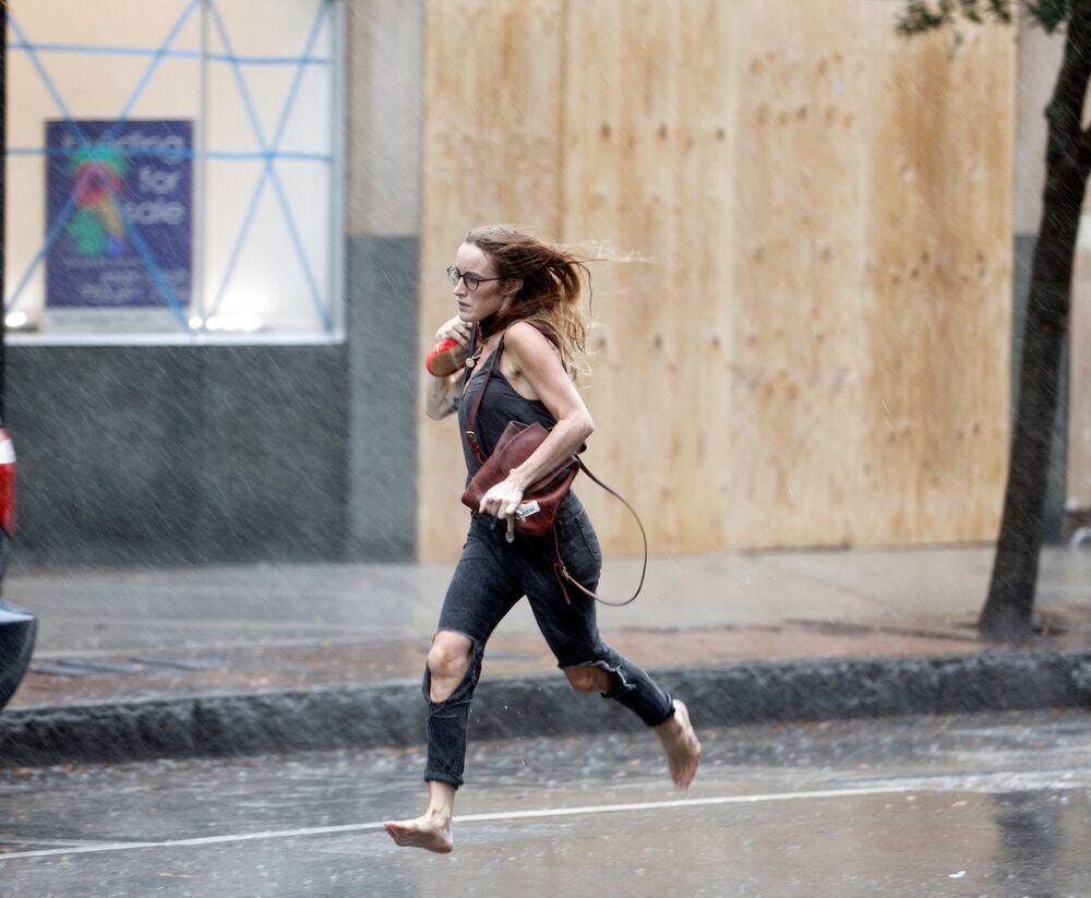 Moça correndo descalça durante o furacão Florence em Wilmington, Carolina do Norte