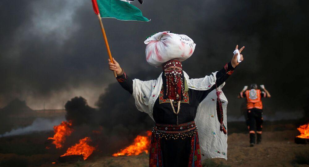 Mulher com uma bandeira palestina durante um protesto contra o bloqueio da Faixa de Gaza por Israel