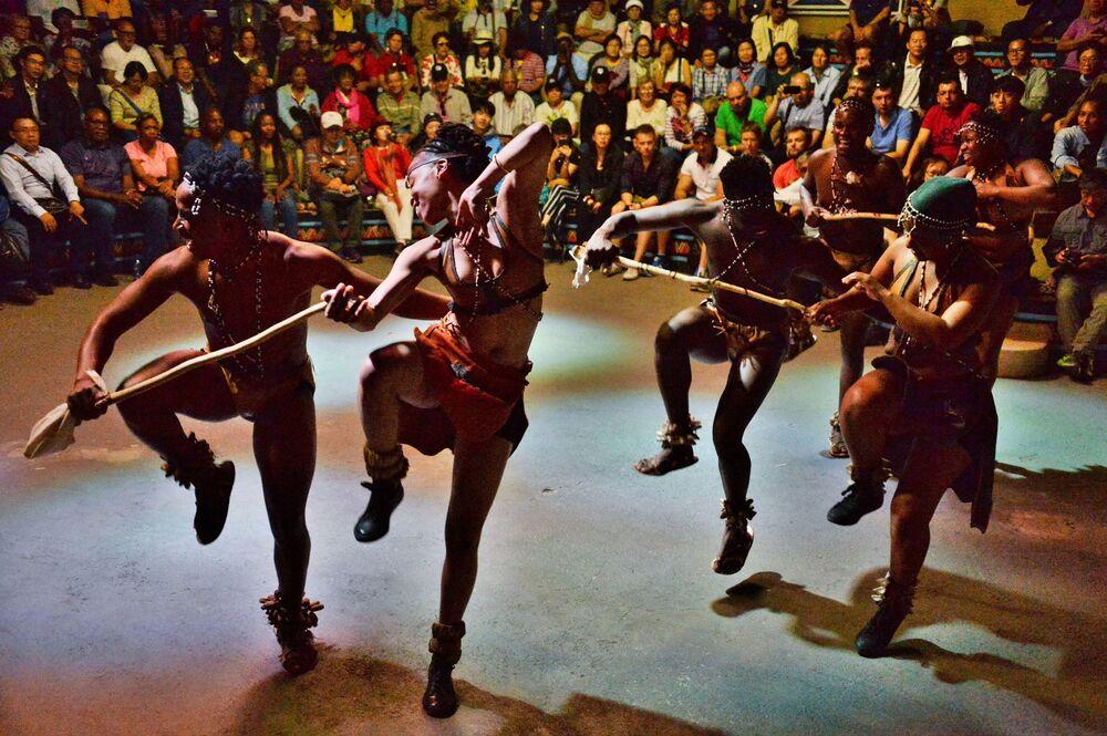 Povos africanos apresentando danças tradicionais para visitantes do centro de cultura africana Lesedi, África do Sul.