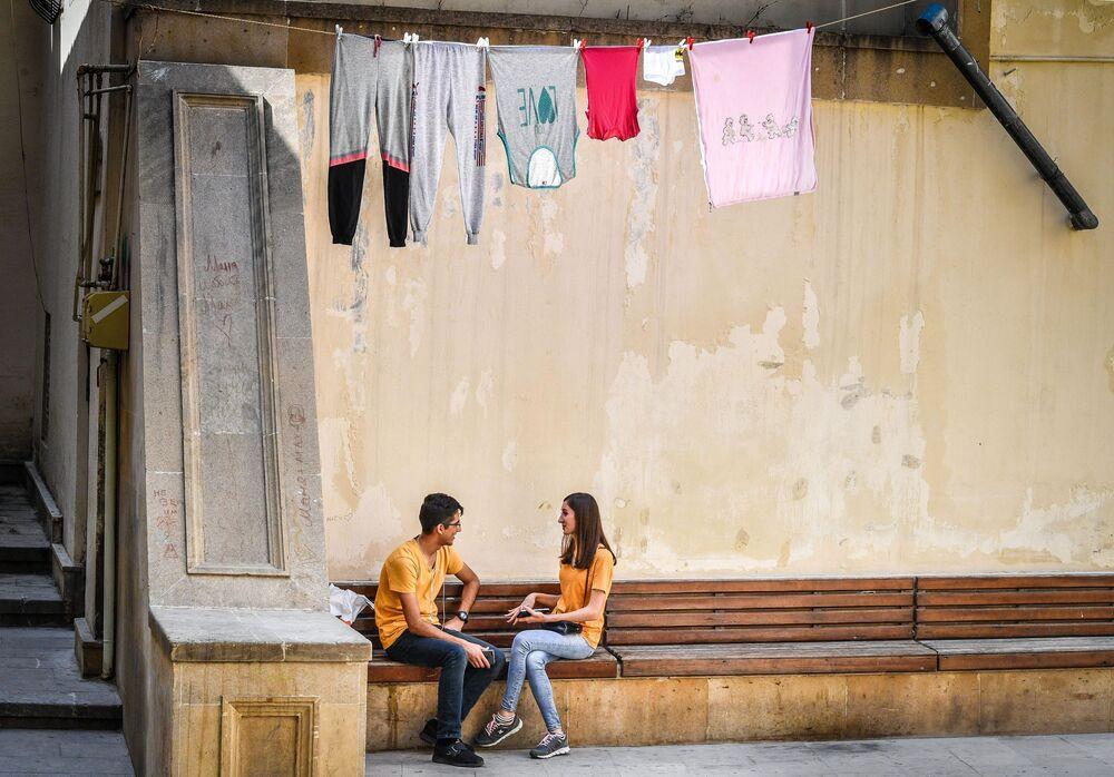 Jovens em um banco na cidade azeri de Baku.