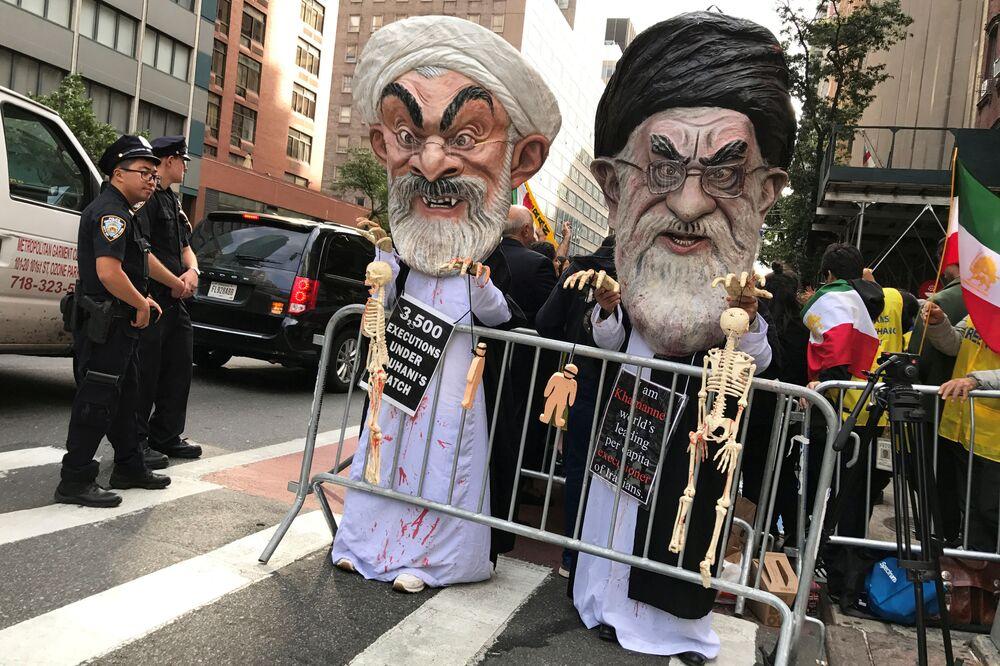 Pessoas usando máscaras do aiatolá Ali Khamenei e do presidente iraniano Hassan Rouhani protestando contra a política do Irã, em Nova York.