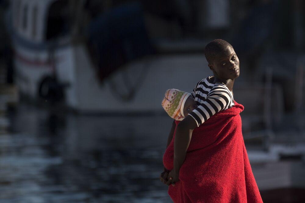 Refugiada carregando bebê nas costas ao chegar ao porto espanhol de Málaga após a guarda costeira espanhola ter salvo um barco inflável com 117 migrantes.
