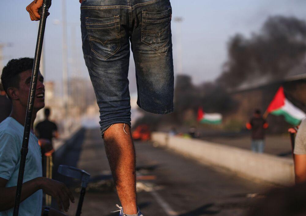 Palestino com perna amputada durante protestos na fronteira entre Israel e Faixa de Gaza.