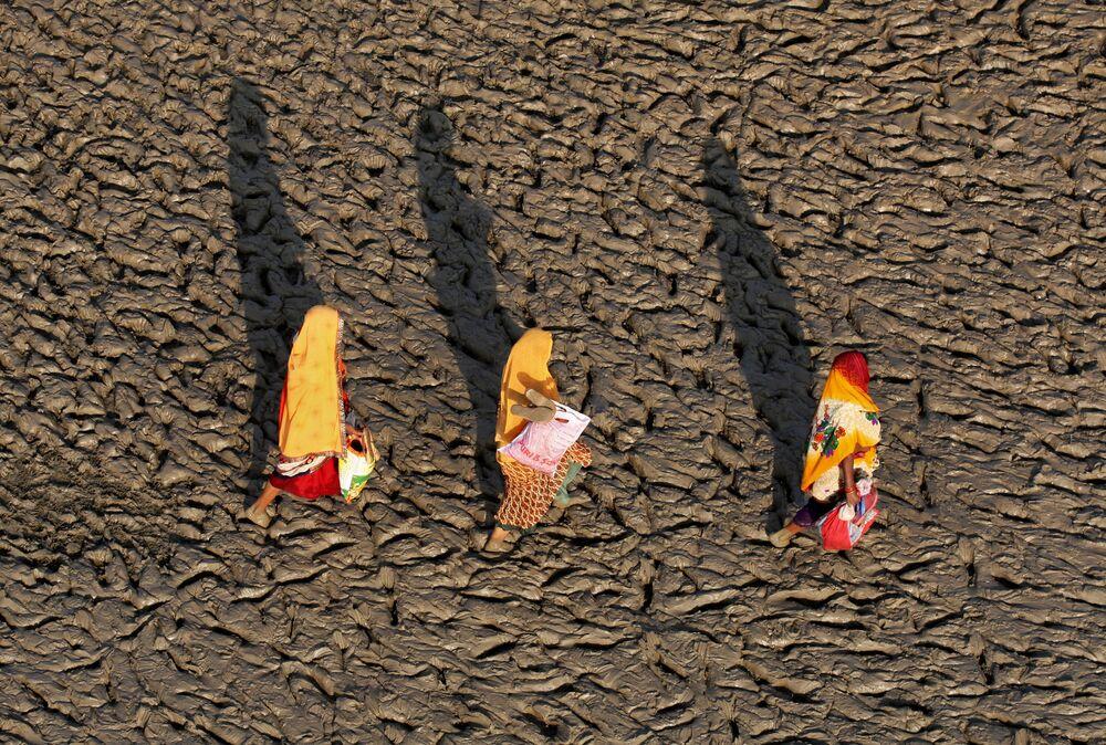 Mulheres caminhando pela margem do rio Ganges após terem realizado o mergulho sagrado, Índia.