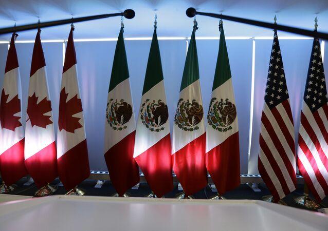 Bandeiras nacionais representando o Canadá, o México e os EUA são iluminadas por luzes do palco do Acordo de Livre Comércio da América do Norte, NAFTA, renegociações na Cidade do México..