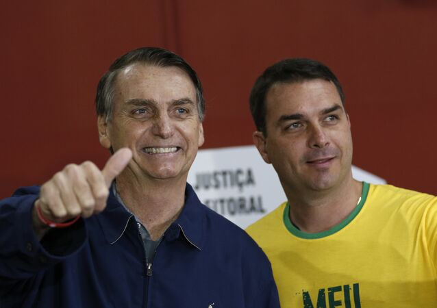 Candidato à presidência do Brasil, Jair Bolsonaro (PSL), vota no Rio de Janeiro junto ao seu filho Flávio, em 7 de outubro de 2018