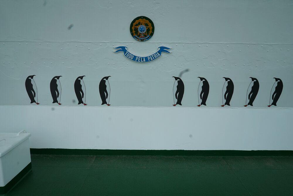 Desenhos de pinguins representando o número de viagens do navio polar Almirante Maximiano à Antártica