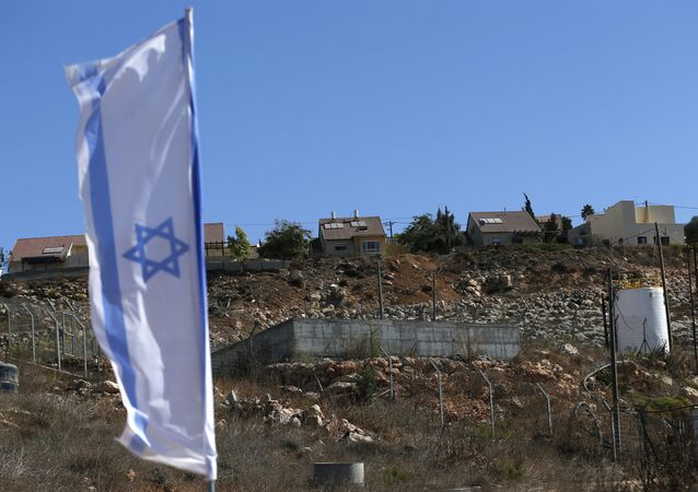 Bandeira nacional israelense próxima a unidades de alojamento novas no estabelecimento judaico de Shilo na Cisjordânia palestina.