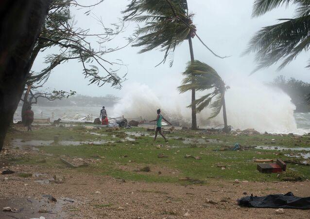Nesta imagem fornecida pelo UNICEF Pacific, as pessoas caminham ao longo da costa, onde detritos são espalhados em Port Vila, Vanuatu, sábado, 14 de março de 2015, após o ciclone Pam
