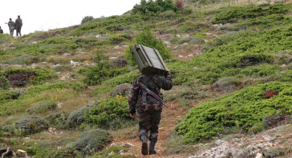 Soldado do Exército sírio carregando armamento ao norte da província síria de Latakia