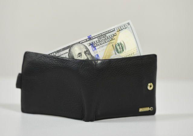 Carteira com uma nota de dólar por dentro (foto referencial)