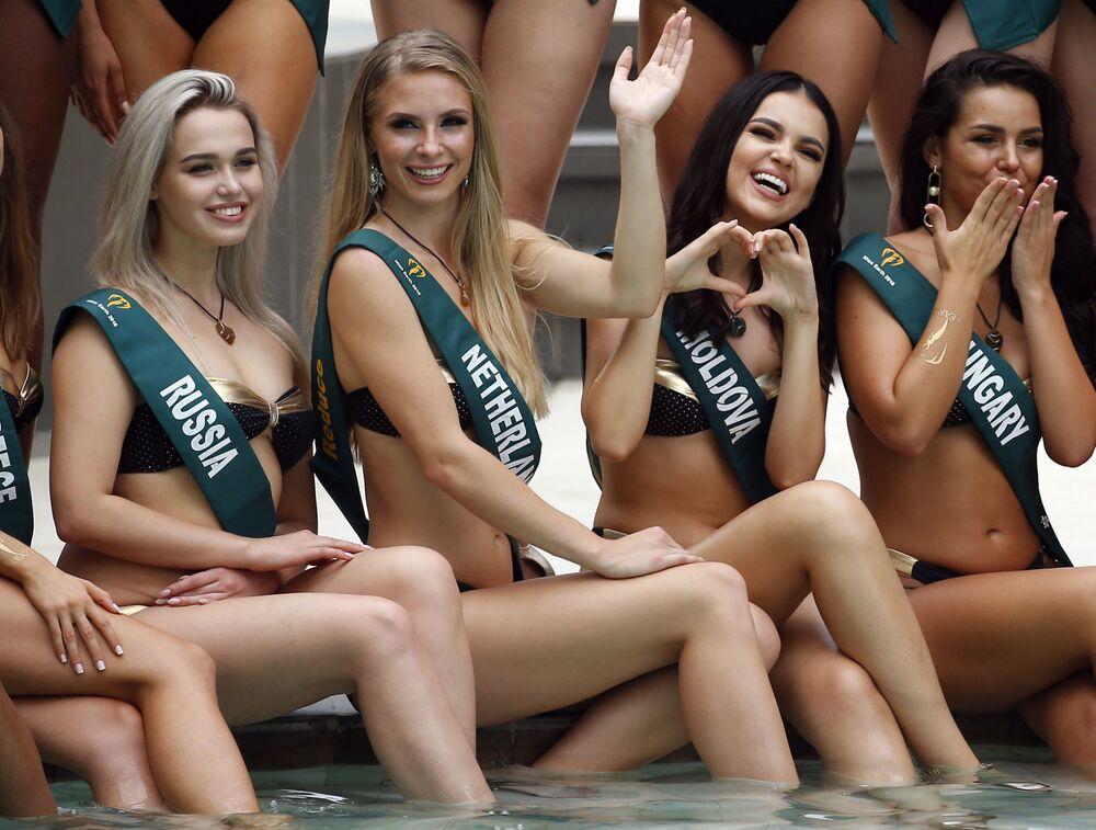 Representantes da Rússia, Holanda, Moldávia e Hungria posam para fotos sentadas à beira da piscina durante apresentação do Miss Terra 2018, na capital filipina de Manila