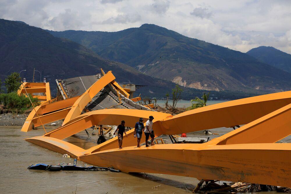 Pessoas andam por uma ponte destruída pelo terremoto, na cidade indonésia de Palu