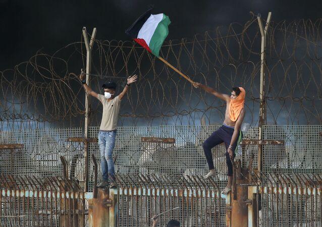 Manifestantes palestinos desfraldam bandeira na fronteira entre Israel e a Faixa de Gaza